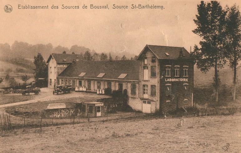 """Établissement des Sources de Bousval vers 1930 : l'usine avec de part et d'autre une aile sur laquelle est indiqué à la peinture """"laboratoire"""" et sur l'autre """"bureau"""". Juste à côté, un tout petit bâtiment sur lequel est inscrit """"source"""""""