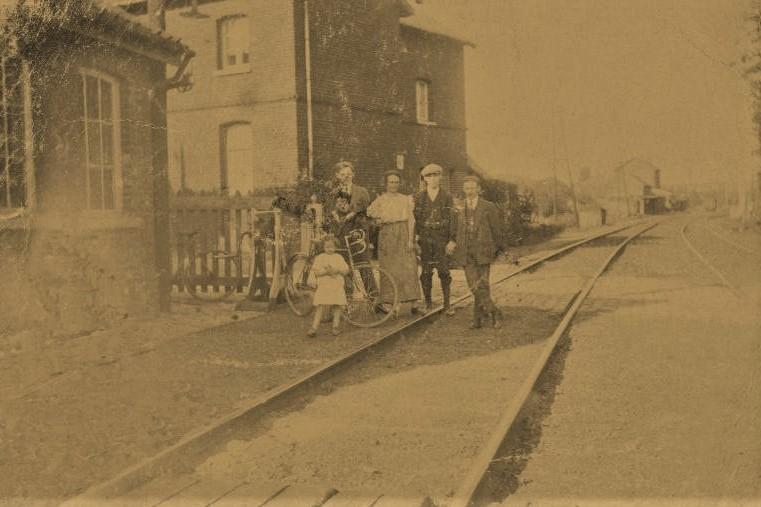 Ancienne carte postale montrant une famille posant près de ligne de chemin de fer n° 141  (passage à niveau de rue de la station, actuelle rue du Grand Arbre)